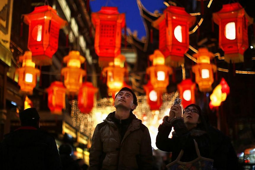 A couple look at Chinese New Year lanterns decorating Yuyuan Garden in downtown Shanghai January 28, 2014. As the Chinese New Year comes around, a difficult question arises for couples: which set of parents to join for the all-important r
