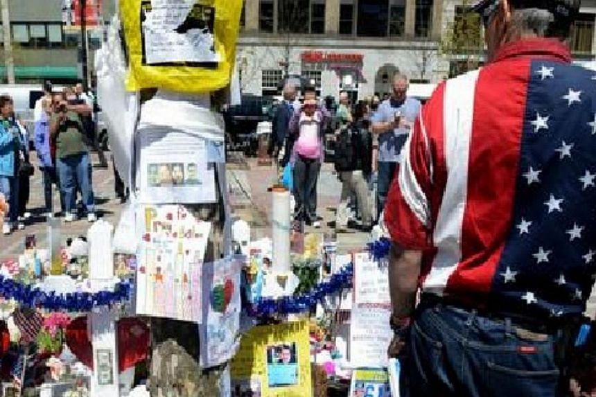 A man with an American flag shirt stands at the memorial site in Copley Square after the deadly attacks on the Boston Marathon on Boylston Street April 30, 2013 in Boston, Massachusetts. -- PHOTO: AFP