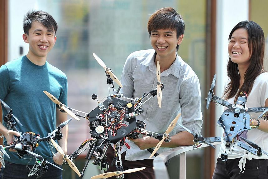 SUTD multi-rotor club members (from left) Ivan Lee Kok Hao, Kyi Hla Win and Goh Chian Yee with their flying creations, which can take aerial photos and videos. -- ST PHOTO: LIM YAOHUI