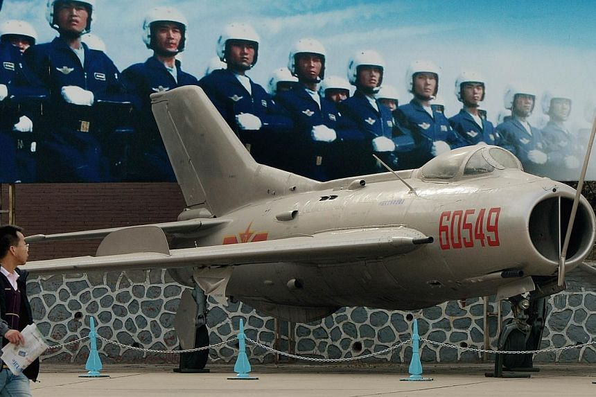 """A man walks past a poster of Chinese airmen beside a Chinese-made J6 fighter jet on display at the People's Liberation Army Aviation Museum in Beijing. China which recently declared an """"air defence identification zone"""" (ADIZ) covering East China Sea"""