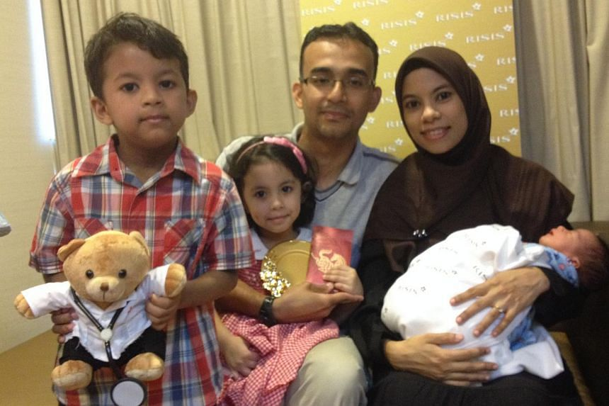 (From right) Madam Sharifah Nurulhuda Mohtar Bahron and Mr Syed Omar Alhadad, with their newborn, four-year-old daughter Sharifah Husnaa and five-year-old son Syed Hamzah. -- ST PHOTO: NUR ASYIQIN MOHAMMAD SALLEH