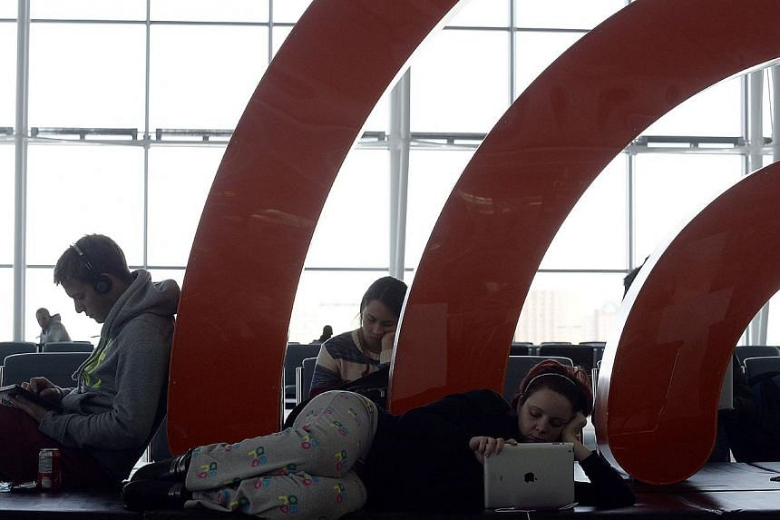 Travellers pass the time at Pearson International Airport Terminal One in Toronto, on Jan 7, 2014. As a trial run for the NSA and other foreign intelligence agencies, Canadian intelligence collected data from Canadian travellers who passed through ma