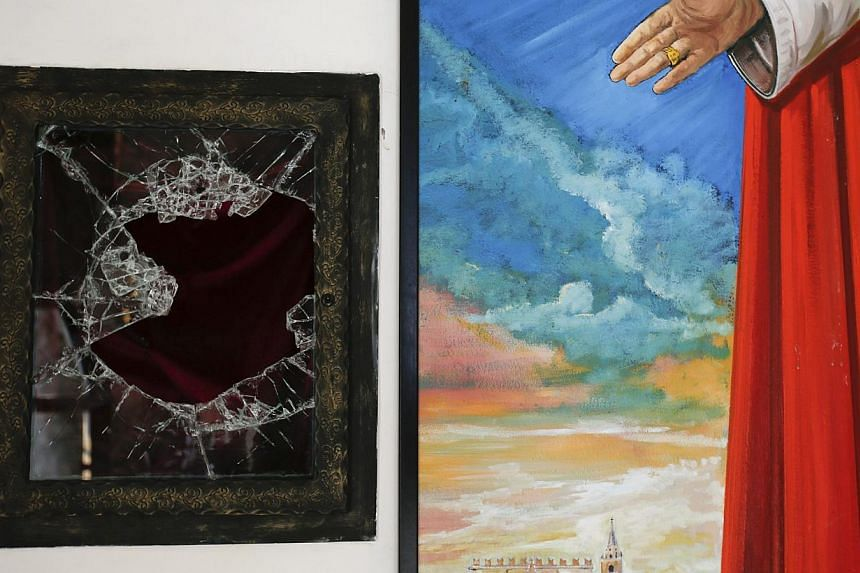 A broken glass of a niche where the reliquary with the blood of the late Pope John Paul II was located is seen next to a painting of the late Pope in the small mountain church of San Pietro della Ienca, near the city of L'Aquila, on Jan 28, 2014. Pol