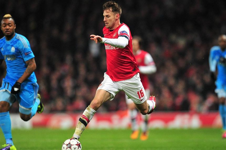 Arsenal's Welsh midfielder Aaron Ramsey (centre) runs with the ball during the UEFA Champions League group F football match between Arsenal and Olympique de Marseille at the Emirates Stadium in London, on Nov 26, 2013. Arsenal midfielder Aaron Ramsey