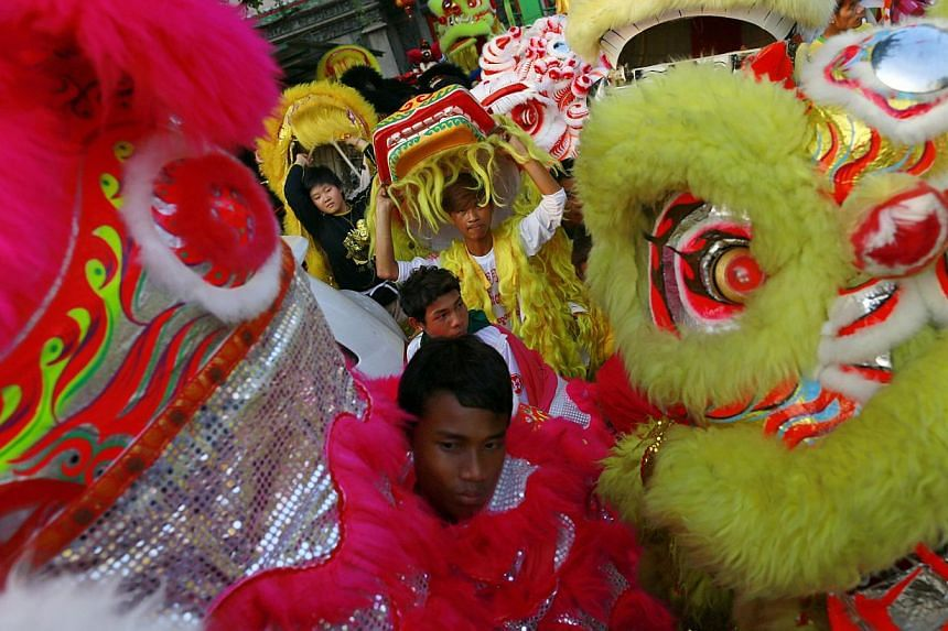 Men hold Chinese lion dance costume heads as they celebrate ahead of Chinese New Year in Yangon's Chinatown, on Jan 30, 2014. -- PHOTO: REUTERS