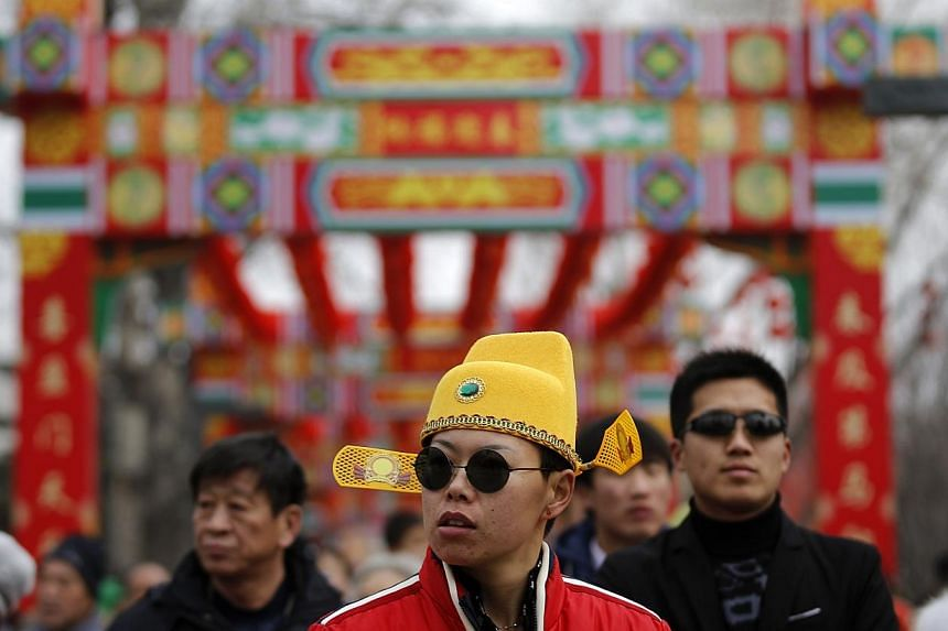 People burn incense for good fortune on the first day of the Chinese New Year at Yonghegong Lama Temple, in Beijing, on Jan 31, 2014. -- PHOTO: REUTERS