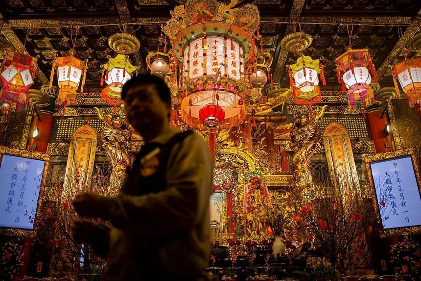 A man walks past an altar at the Wong Tai Sin Temple to welcome the Chinese New Year of the horse in Hong Kong, on Jan 30, 2014. -- PHOTO: AFP
