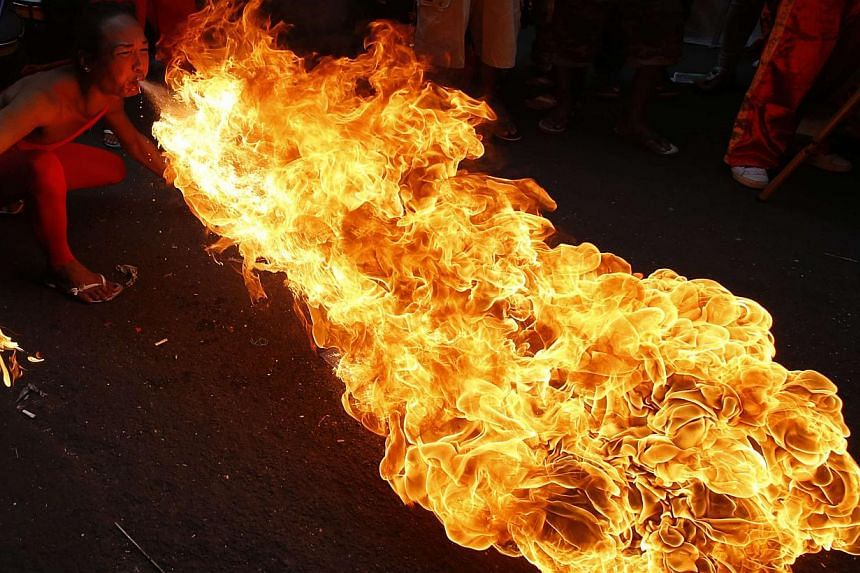 A performer blows fire during the Chinese New Year celebration in Manila's Chinatown, on Jan 31, 2014. -- PHOTO: REUTERS