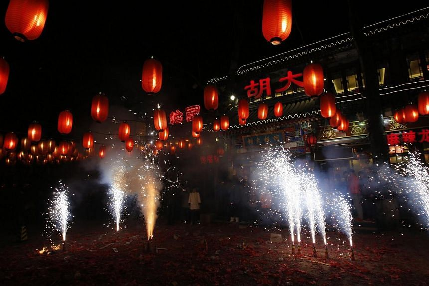 People watch fireworks to celebrate the start of the Chinese New Year in front of a restaurant in Beijing, on Jan 31, 2014. Fireworks illuminated the skies across Asia and millions of families gathered together on Friday, Jan 31, 2014, to usher in th
