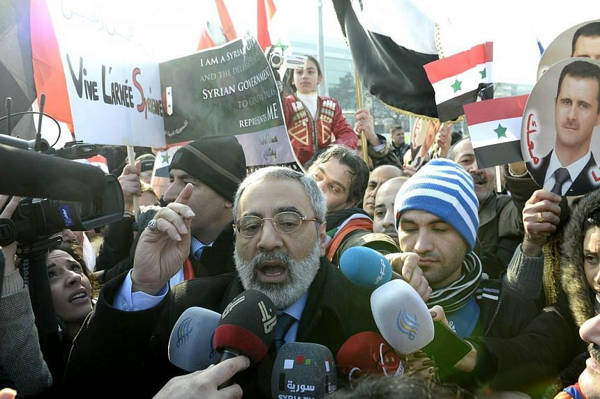 """Syrian Information Minister Omran al-Zohbi (centre front) addresses the media as he takes part to a demonstration of pro-Syrian regime protesters, on Jan 31, 2014, in front of the United Nations headquarters in Geneva. Damascus will make """"no concessi"""