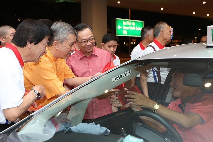 Health Minister Gan Kim Yong (in red), along with taxi leaders from the National Taxi Association, gave out goodie bags and hongbao to taxi drivers at Changi Airport on Friday morning, Jan 31, 2014, to thank them for working on the first day of Chine