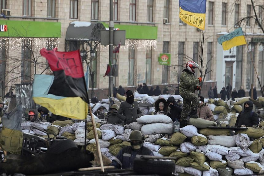 "Anti-government protesters gather at a barricade at the site of clashes with riot police in Kiev, on Jan 30, 2014. Ukraine's armed forces on Friday, Jan 31, 2014, urged embattled President Viktor Yanukovych to take ""urgent steps"" to ease the crisis i"