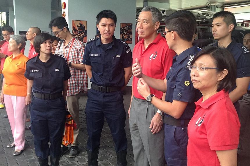 PM Lee Hsien Loong watches drills conducted by the Singapore Civil Defence Force personnel and hands out oranges. -- ST PHOTO: GOH CHIN LIAN