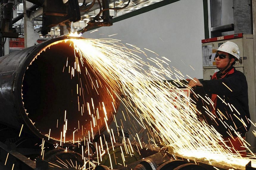 A worker operates a machine to cut a pipeline at a factory in Qingdao, Shandong province on Nov 29, 2013. China's official gauge of its manufacturing sector slipped to a five-month low in January, the government announced on Saturday, confirming a sl