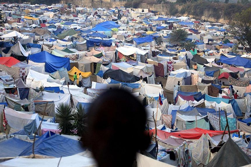 A boy stands at a makeshift camp on the grounds of the Petionville Golf Course in Port-au-Prince, Haiti in this Jan 26, 2010. The tents are gone and clean up crews are grooming the grounds of the Petionville country club golf course, which served as