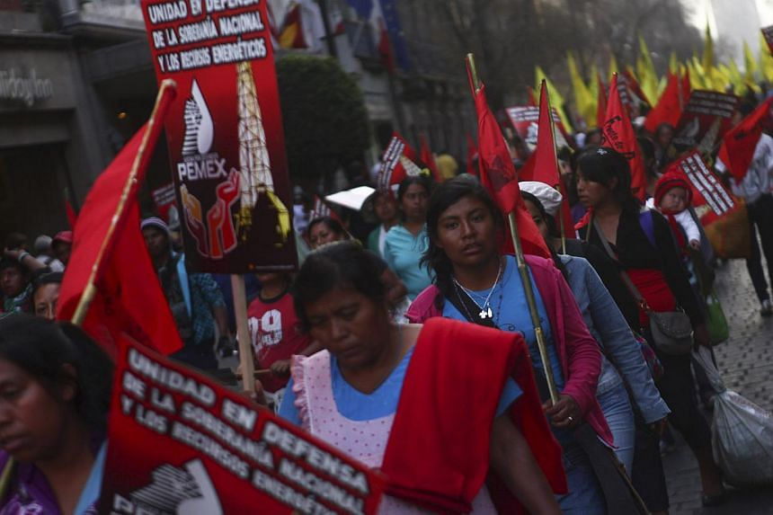 Civil organisations and supporters of the party of the Democratic Revolution (PRD) wave flags during a march to protest against the privatization of the state-oil monopoly Pemex at Zocalo square in Mexico City on Jan 31, 2014. Tens of thousands of pe
