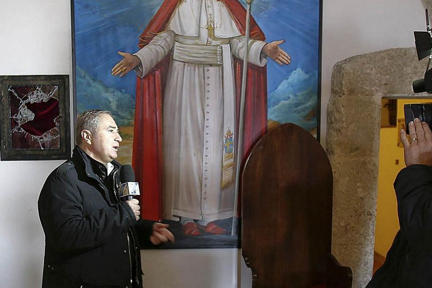 A reporter speaks in front of a broken glass of a niche in the small mountain church of San Pietro della Ienca, near the city of L'Aquila, on Jan 28, 2014.Italian police have recovered part of a religious relic stained with Polish pope John Pau