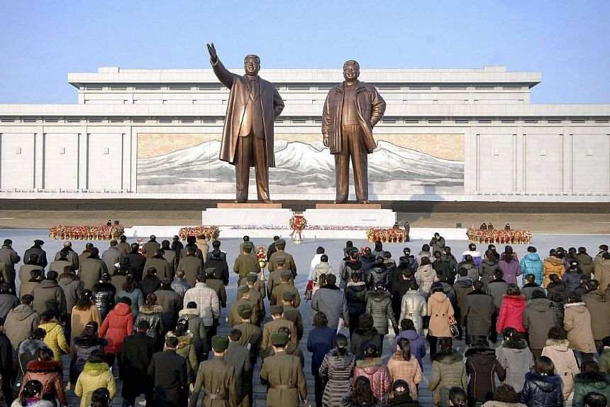 People gather in front of the statues of North Korea's founder Kim Il Sung and former and late leader Kim Jong Il as they mark the Lunar New Year in this undated photo released by North Korea's Korean Central News Agency (KCNA) in Pyongyang January 3