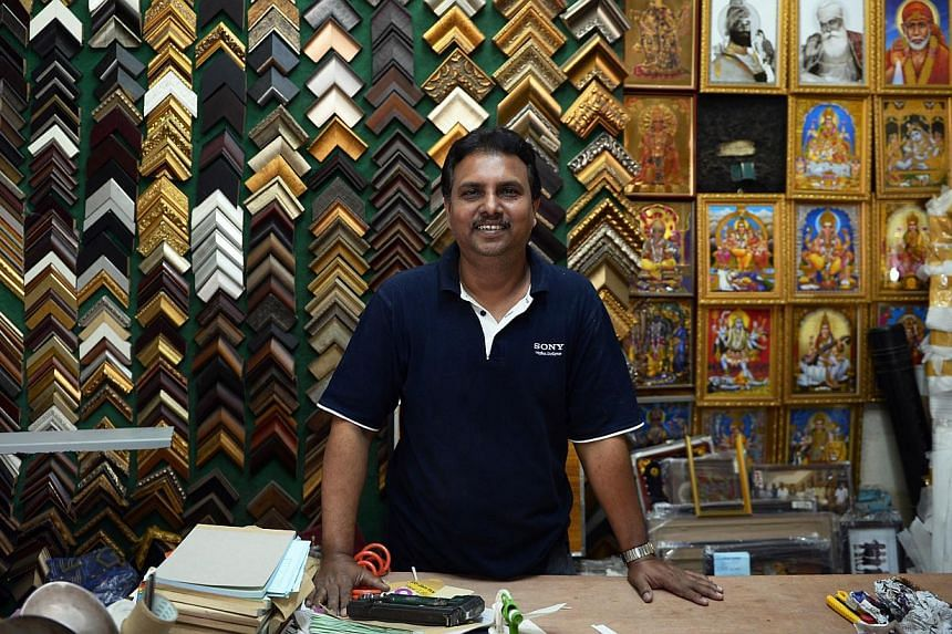 Mr Syed Yoosuf hopes the calmer situation will result in more customers for his shop, which sells portraits of deities. -- ST PHOTO: MARK CHEONG