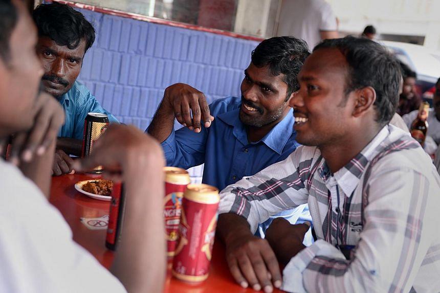 (Clockwise from left) Workers Murugan Ponnusamy, 30; Mani Munusamy, 26; Velu Arumugam, 31; and Kuberan Mani, 25, having a beer last Sunday at Spice Box restaurant at about 4pm. The three brothers and their uncle, Mr Munusamy, still meet every Sunday