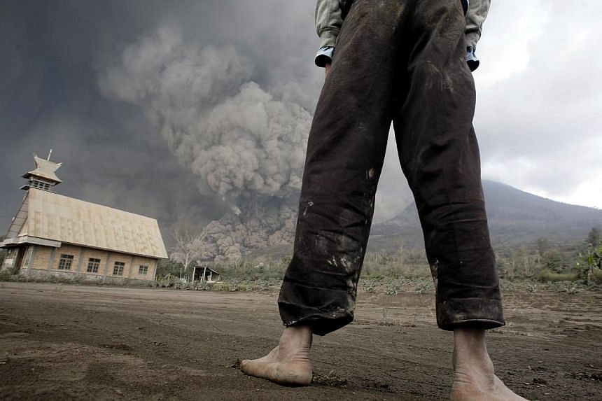 A resident looks on at giant volcanic ash clouds from a village in Karo district during the eruption of Mount Sinabung volcano located in Indonesia's Sumatra island on February 1, 2014. Fourteen people, including four schoolchildren, were killed Febr