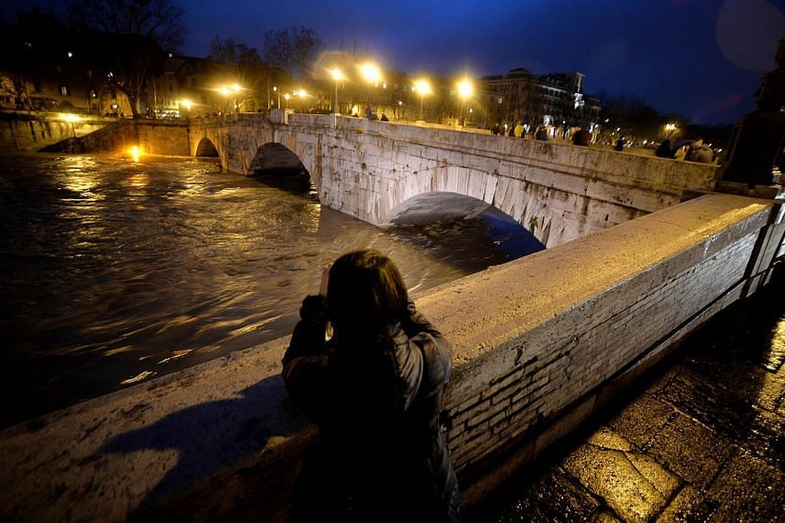 A couple looks the Tiber river by downtown Rome's Tiberina's Island, as the river's water level is rising following heavy rains in the region on Feb 1, 2014. -- PHOTO: AFP