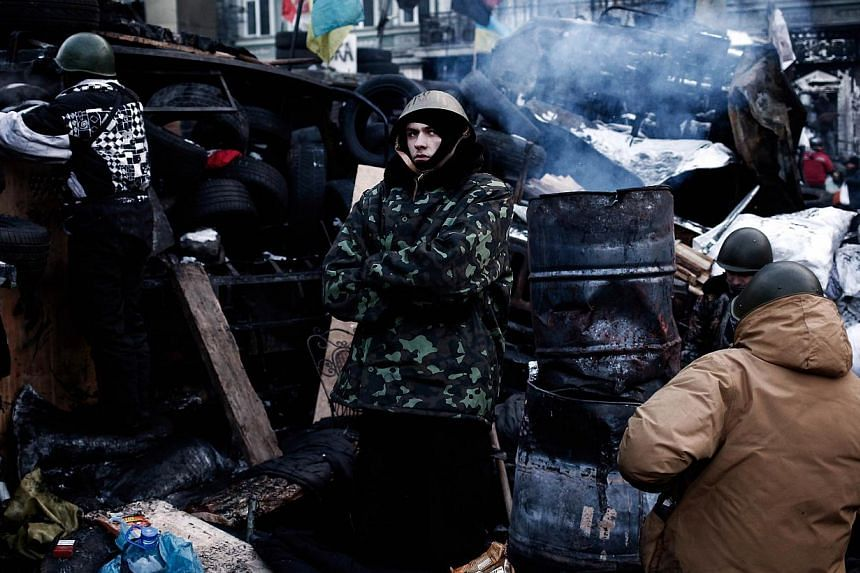 Anti-government protesters stand guard at a barricade in Kiev on Feb 1, 2014. -- PHOTO: AFP