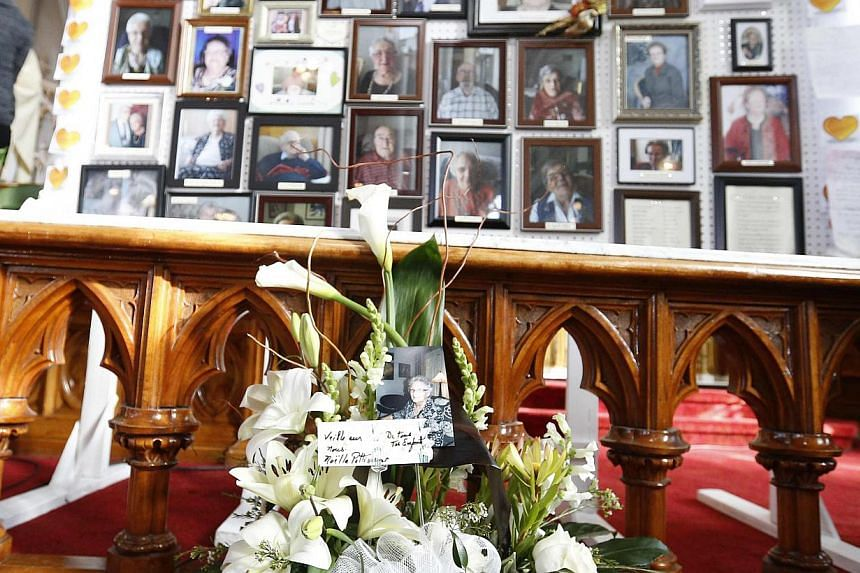 Pictures are displayed during a memorial ceremony for the victims of the Residence du Havre fire at the Decollation-de-Saint-Jean-Baptiste church in L'Isle Verte, Quebec on Feb 1, 2014. -- PHOTO: REUTERS