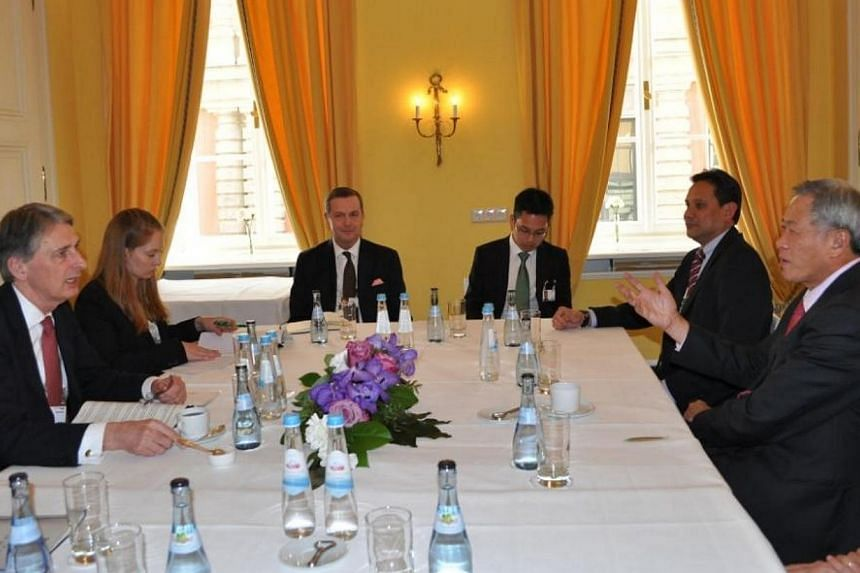 Dr Ng (right) meeting with UK Secretary of State for Defence Philip Hammond on the sidelines of the conference.-- PHOTO: MINDEF
