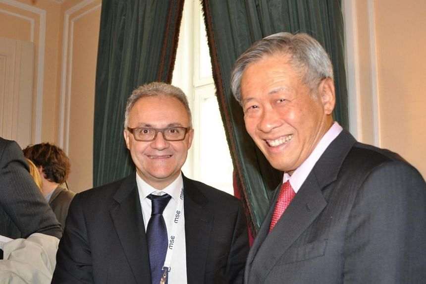 Dr Ng (right) meeting with Italian Minister of Defence Mario Mauro (left) on the sidelines of the conference.-- PHOTO: MINDEF
