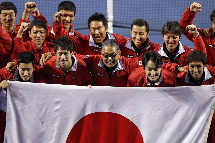 Japan's Yuichi Sugita (front row left to right), Kei Nishikori, captain Minoru Ueda, Go Soeda and Yasutaka Uchiyama celebrate with their team after defeating Canada during their Davis Cup world group first round tennis match in Tokyo, on Sunday, Feb