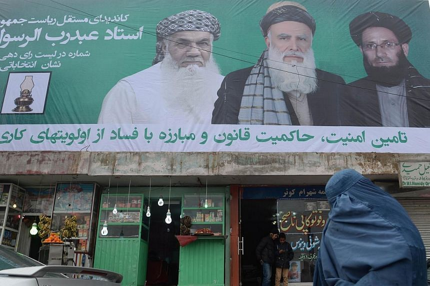 A burqa-clad Afghan pedestrian walks past an election campaign poster of former Islamist warlord, Abdul Rasul Sayyaf during the first day of the presidential election campaign in Kabul, on Feb 2, 2014.Afghanistan's election campaign kicks off o