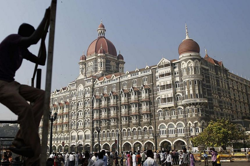 A man sits on a scaffolding erected for a stage as tourists walk near the Taj Mahal Hotel which was one of the targets of the November 2008 attacks, in Mumbai, on Nov 26, 2013.Tourists travelling to India from up to 180 countries will no