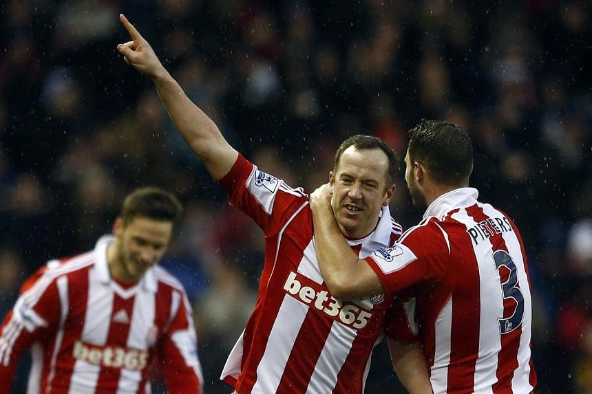 Stoke City's Charlie Adam (centre) celebrating with team mate Erik Pieters (tight) after scoring a goal against Manchester United during their English Premier League match at the Britannia Stadium in Stoke-on-Trent on February 1, 2014.