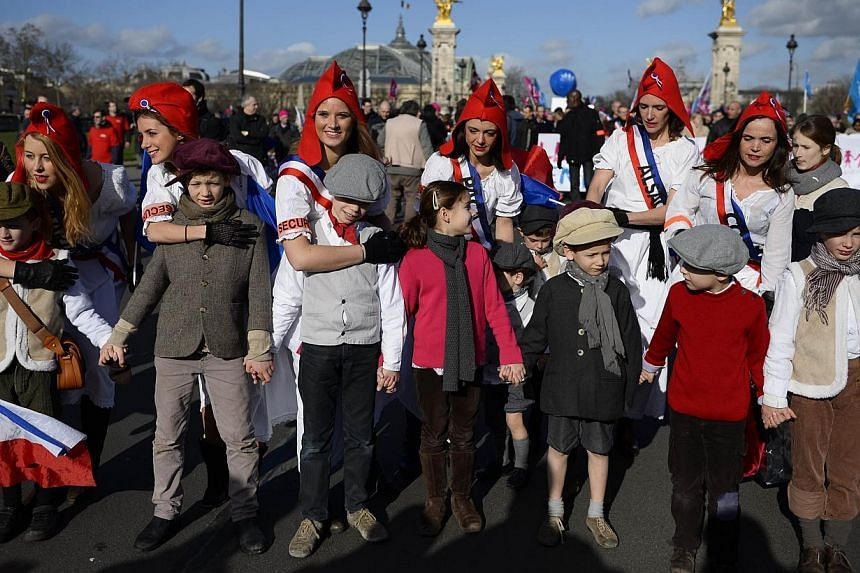 """Women wearing a Phrygian cap demonstrate with supporters of the """"La Manif Pour Tous"""" (Protest for Everyone) movement to defend their vision of the traditional family, on Feb 2, 2014, in Paris. -- PHOTO: AFP"""