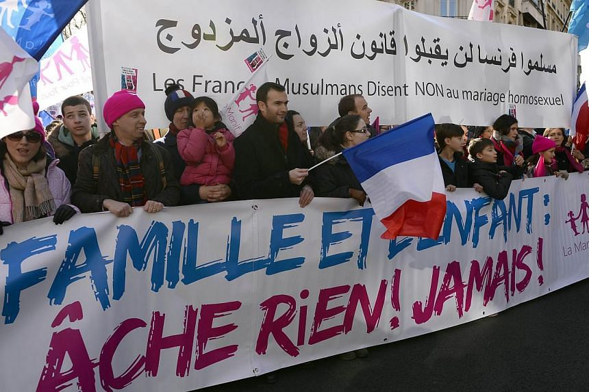 """Supporters of the """"La Manif Pour Tous"""" (Protest for Everyone) movement hold a banner reading """"Family and child: we will not give up! Never!"""" as they protest to defend their vision of the traditional family. -- PHOTO: AFP"""