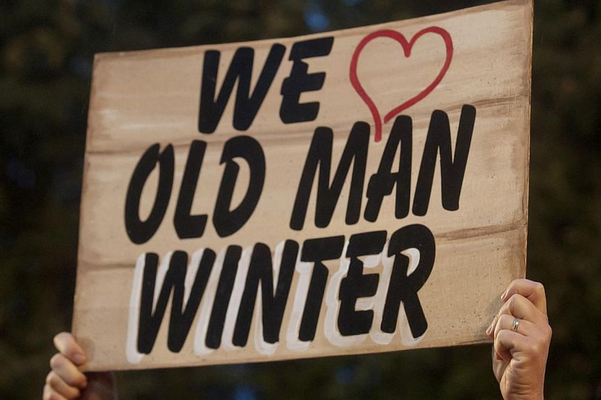 A member of the Groundhog Club holds up a sign referencing the six more weeks of winter predicted by groundhog Punxsutawney Phil during the 128th annual Groundhog Day celebration on Gobbler's Knob in Punxsutawney, Pennsylvania on Feb 2, 2014. -- PHOT