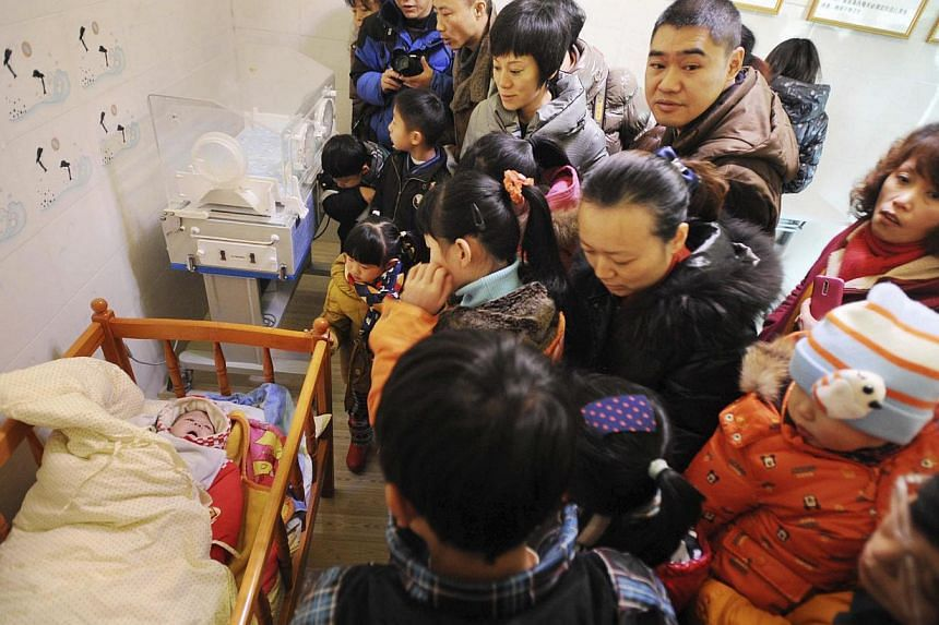 """Residents visit an abandoned baby (left) lying in a crib at a baby hatch in Guiyang, Guizhou province on Jan 12, 2014. Dozens of babies have been secretly dropped off at """"baby safety islands"""", or """"baby hatches"""", set up since late last year under a sc"""