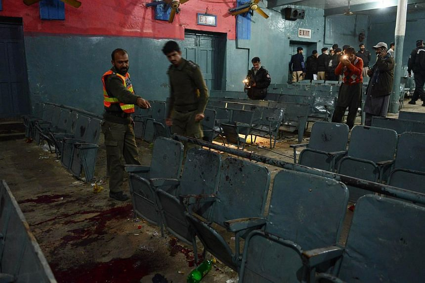 Pakistani investigators inspect the site of a grenade attack in a cinema in Peshawar on Feb 2, 2014. At least four people were killed and 31 wounded late Sunday when unidentified attackers hurled two grenades at a cinema in north-west Pakistan, polic