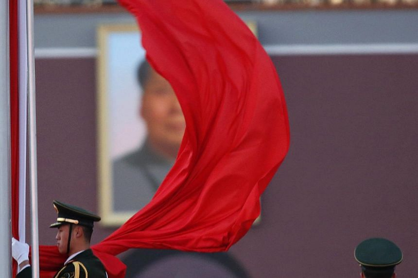 A paramilitary policeman holding the Chinese national flag at a flag lowering ceremony on Tiananmen square next to the Great Hall of the People as the portrait of late Chinese Chairman Mao Zedong is seen in the background in Beijing, on November 11,