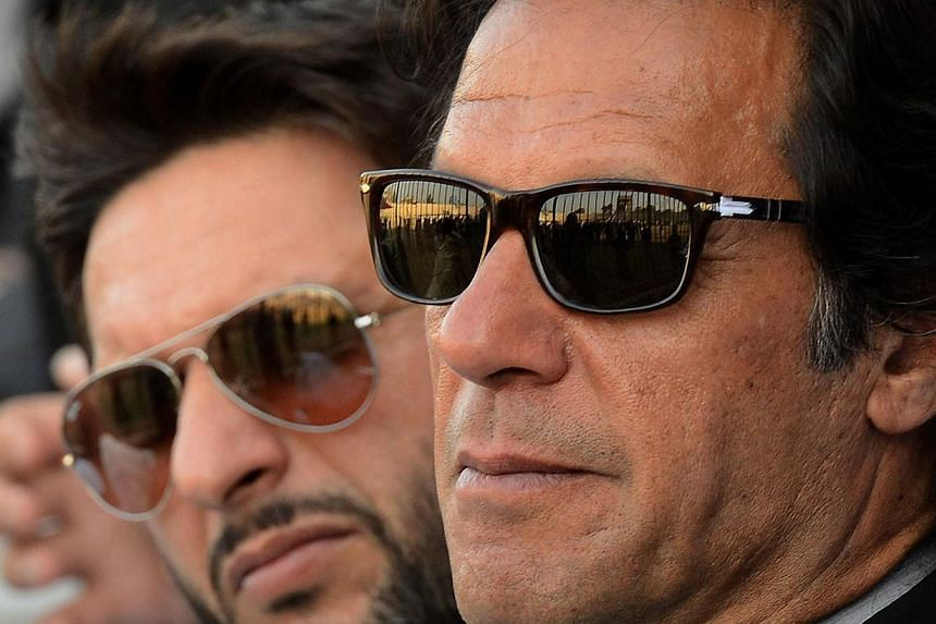 Former Pakistan cricketer turned politician Imran Khan (right) and cricketer Shahid Afridi (left) look on during the launch ceremony of a cricket talent search in Peshawar on January 25, 2014. -- FILE PHOTO: AFP