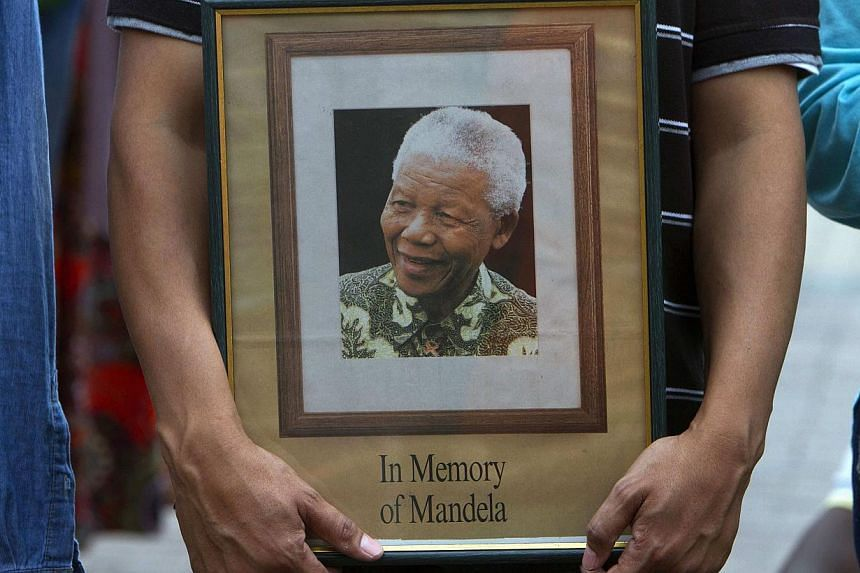 A man holds a tribute photograph as he watches the funeral service for former South African President Nelson Mandela on a large screen television in Cape Town, on Dec 15, 2013. The dying wishes of South Africa's anti-apartheid icon Nelson Mandela wil