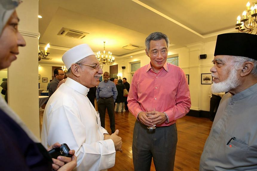 Prime Minister Lee Hsien Loong (in pink) interacting with (from left) Madam Bibi Jan Ayub, Habib Hassan Alatas and Syed Isa Semait during a two-hour dialogue over the Muslim headscarf held at the Old Police Academy, on Jan 25, 2014 . Prime Minister L