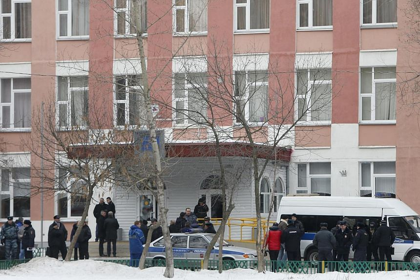 Interior Ministry members in uniform and other authorities gather outside a high school, where a student shot a teacher and a police officer dead and held more than 20 other students hostage, on the outskirts of Moscow, on Feb 3, 2014. -- PHOTO: REUT