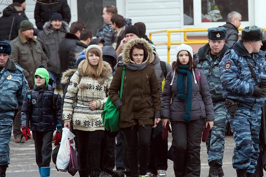 Pupils of Moscow school number 263 leave the building escorted by policemen, on Feb 3, 2014. -- PHOTO: AFP