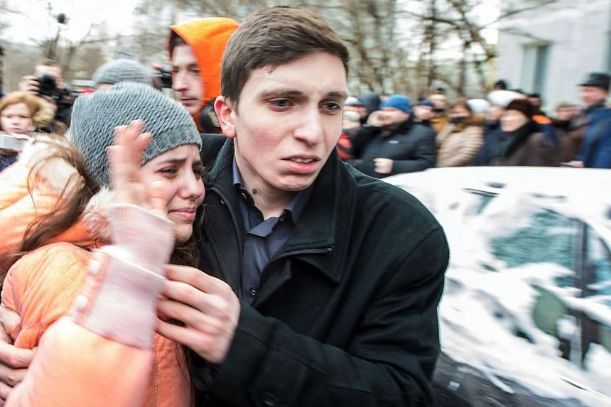 A schoolgirl (left) of school number 263 is hugged by her relative as she left the school building in Moscow, on Feb 3, 2014. -- PHOTO: AFP