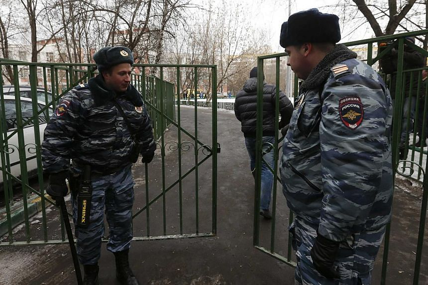 Interior Ministry members stand guard outside the premises of a high school, where a student shot a teacher and a police officer dead and held more than 20 other students hostage, on the outskirts of Moscow, on Feb 3, 2014. -- PHOTO: REUTERS