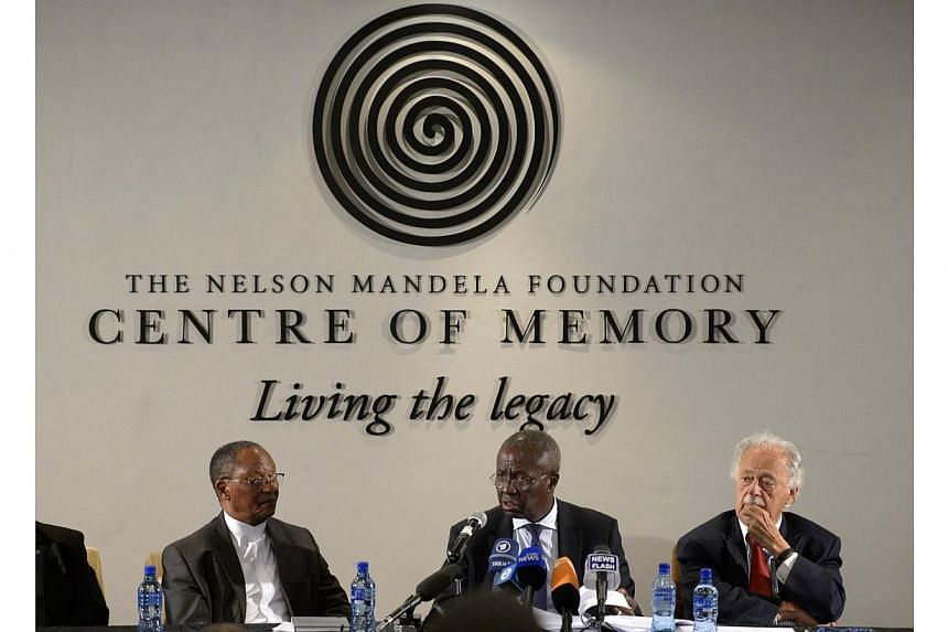 Executor of the Nelson Mandela estate Dikgang Moseneke (centre) talks on Feb 3, 2014, next to fellow executor George Bizos (right) during a press conference, two months after the revered statesman's passed away.Late former South African Preside