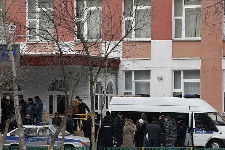 Interior Ministry members in uniform and other authorities gather outside a high school, where a student shot a teacher and police officer dead and held more more than 20 other students hostage, on the outskirts of Moscow, on Monday, Feb 3, 2014.&nbs