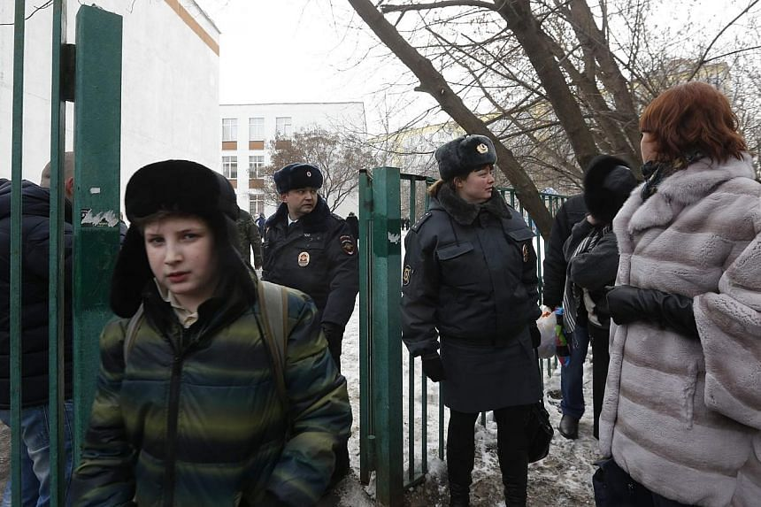 Interior Ministry members evacuate people after an armed student took hostages at a high school on the outskirts of Moscow, on Monday, Feb 3, 2014. An armed student entered a Moscow school on Monday and took more than 20 teenagers hostage, in an